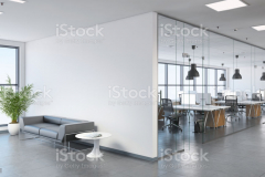 Interior view of a modern office, business template. Left side of the picture is large sofa with a plant and coffee table. Blank wall for copy space. On the right, many office desks with pendant lights above. large windows. gray floor tiles, white walls. Render
